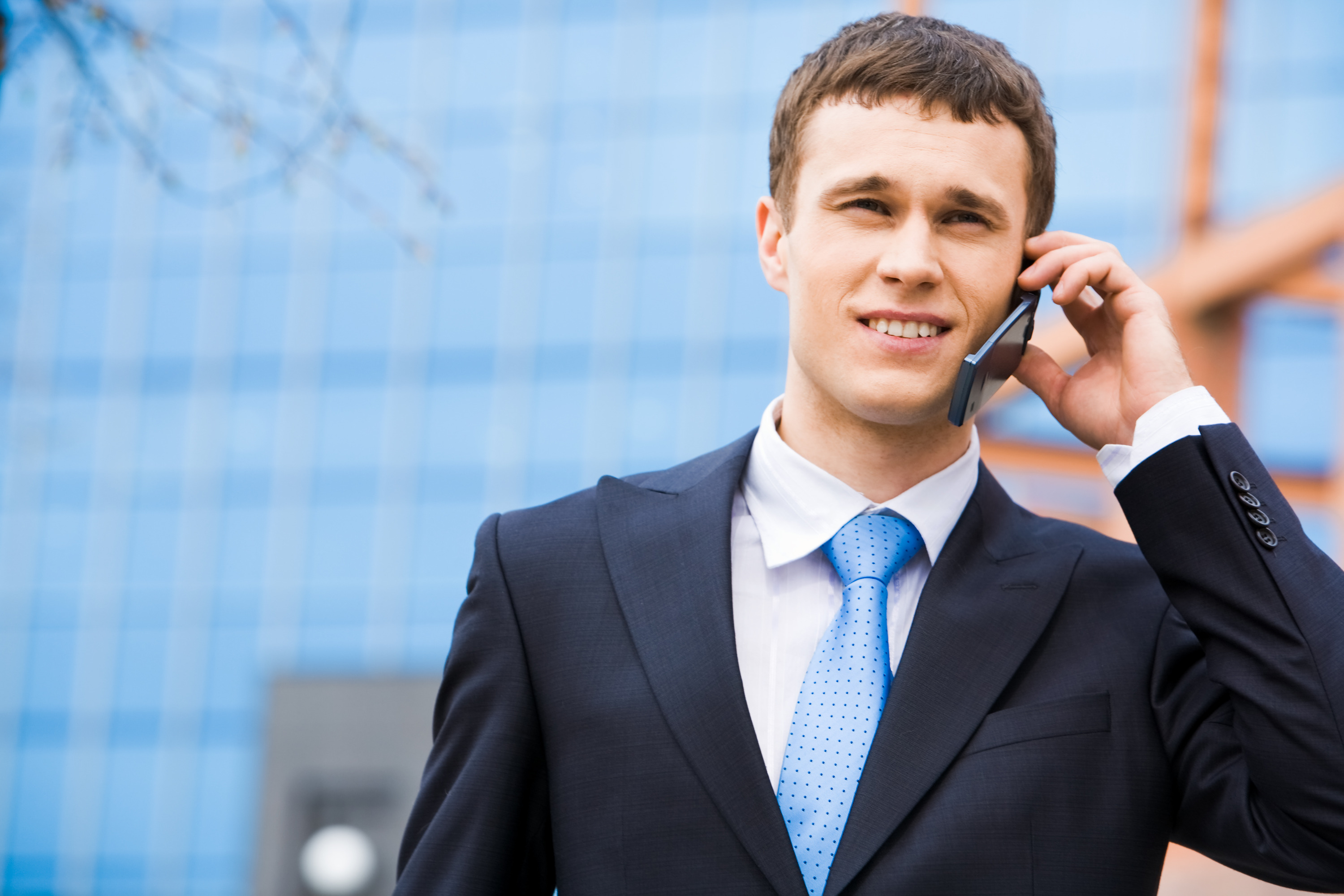 Portrait of successful young man calling on cellular phone outside